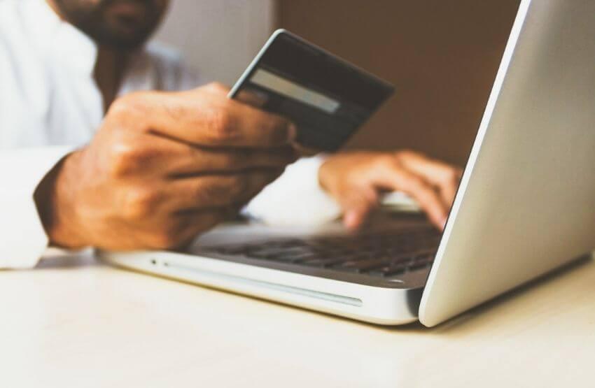Férfi épp online fizet a számítógépén, kezében a bankkártyájával.